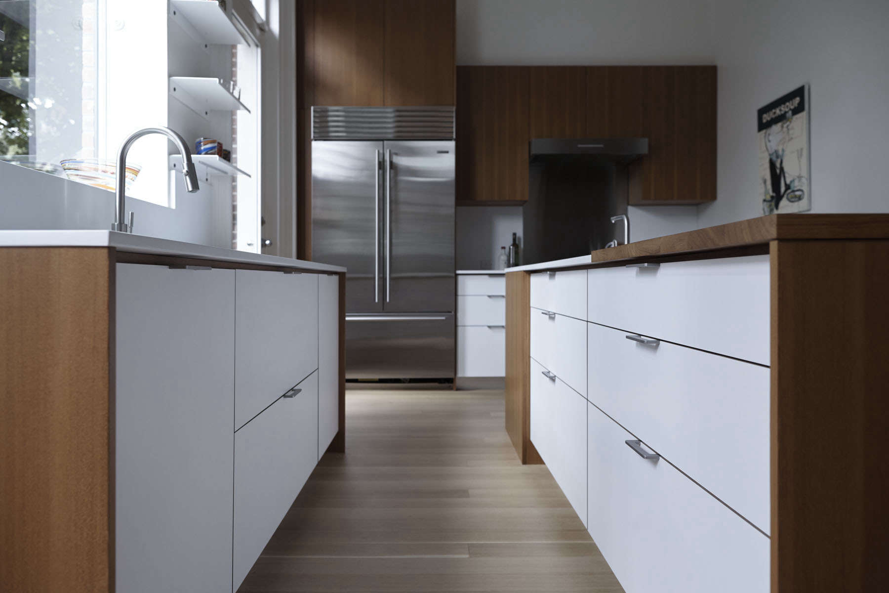 A clean-lined kitchen remodel by architect Shauna McManus and Henrybuilt. The countertops are Caesarstone, the cabinets are teak and white laminate