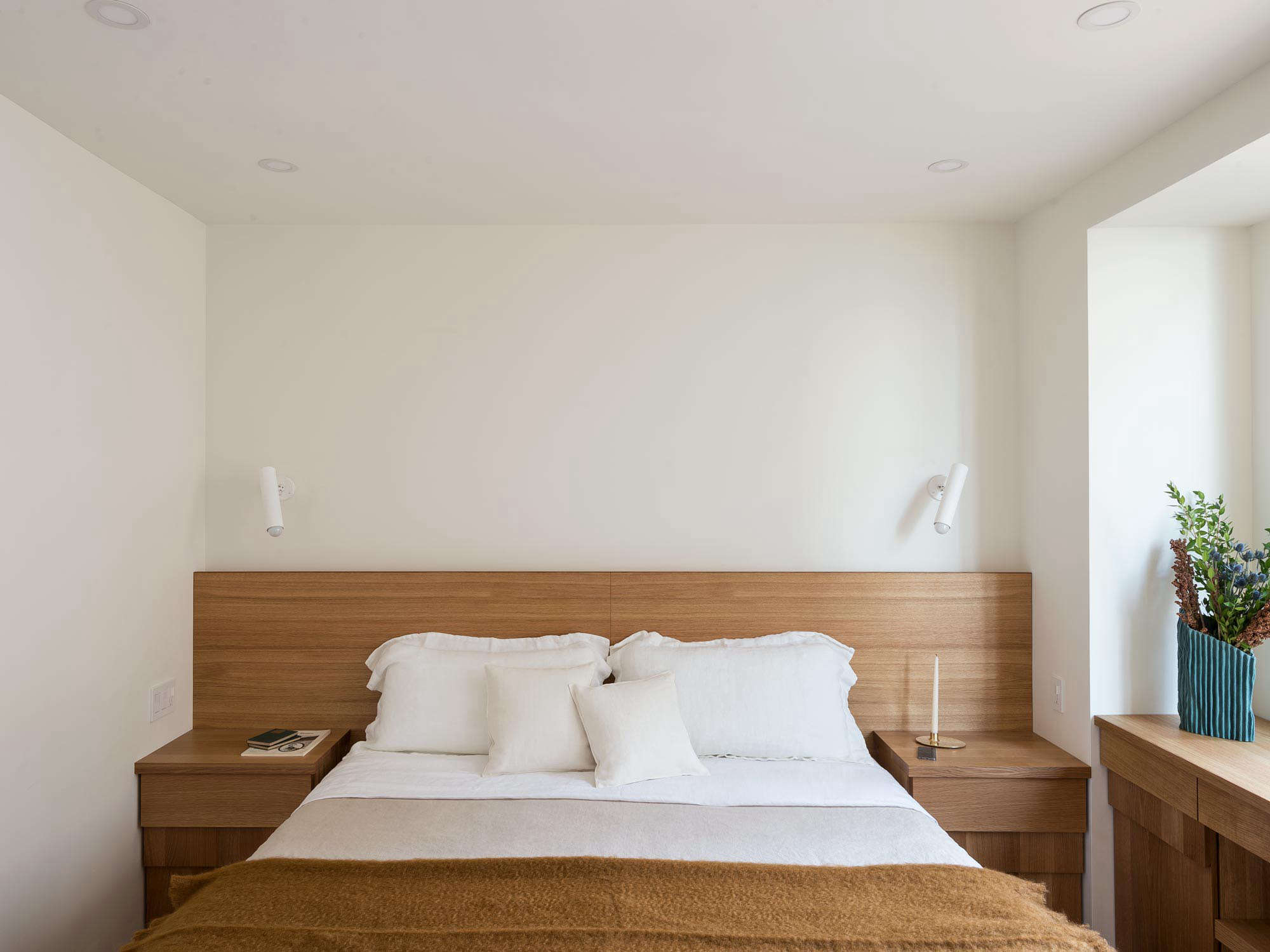 In a small apartment, continuity works well: The architects carried overthe oak millwork in the 12-by-13-foot bedroom, which includes a headboard with built-in side tables.Thesconces are a 1960s design, the2300 CF by Jacques Biny for Lita.