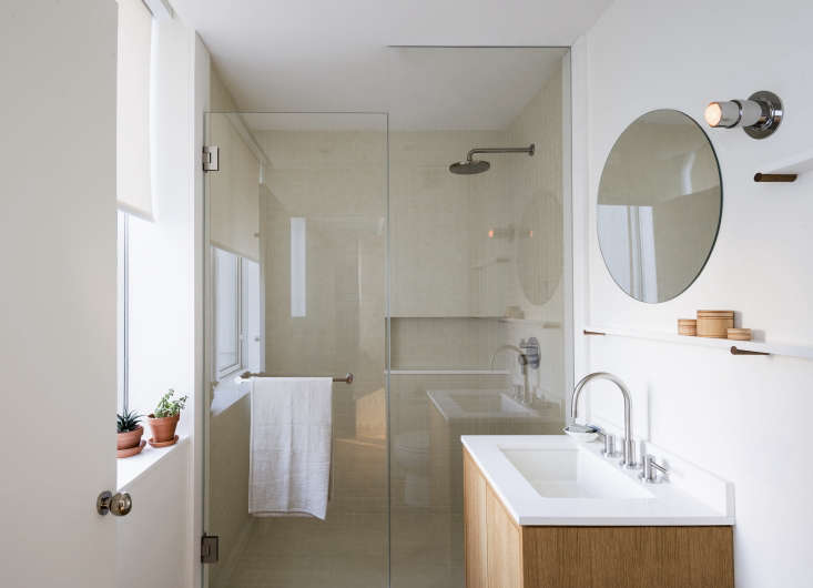 In this bath designed by Workstead, a shallow Corian shelf runs just above the vanity. Photograph by Matthew Williams, courtesy of Workstead, from The Artful Shoebox Apartment, Workstead Edition.