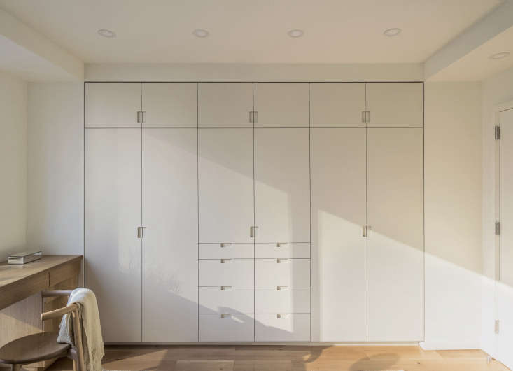 In a Workstead-designed bedroom, built-in closets feature painted millwork with flush pivot doors and routed pulls. The storage wall is fitted with closets, drawers, overhead cupboards, and, in the center, a cabinet that holds the TV. Photograph by Matthew Williams, courtesy of Workstead, from The Artful Shoebox Apartment, Workstead Edition.