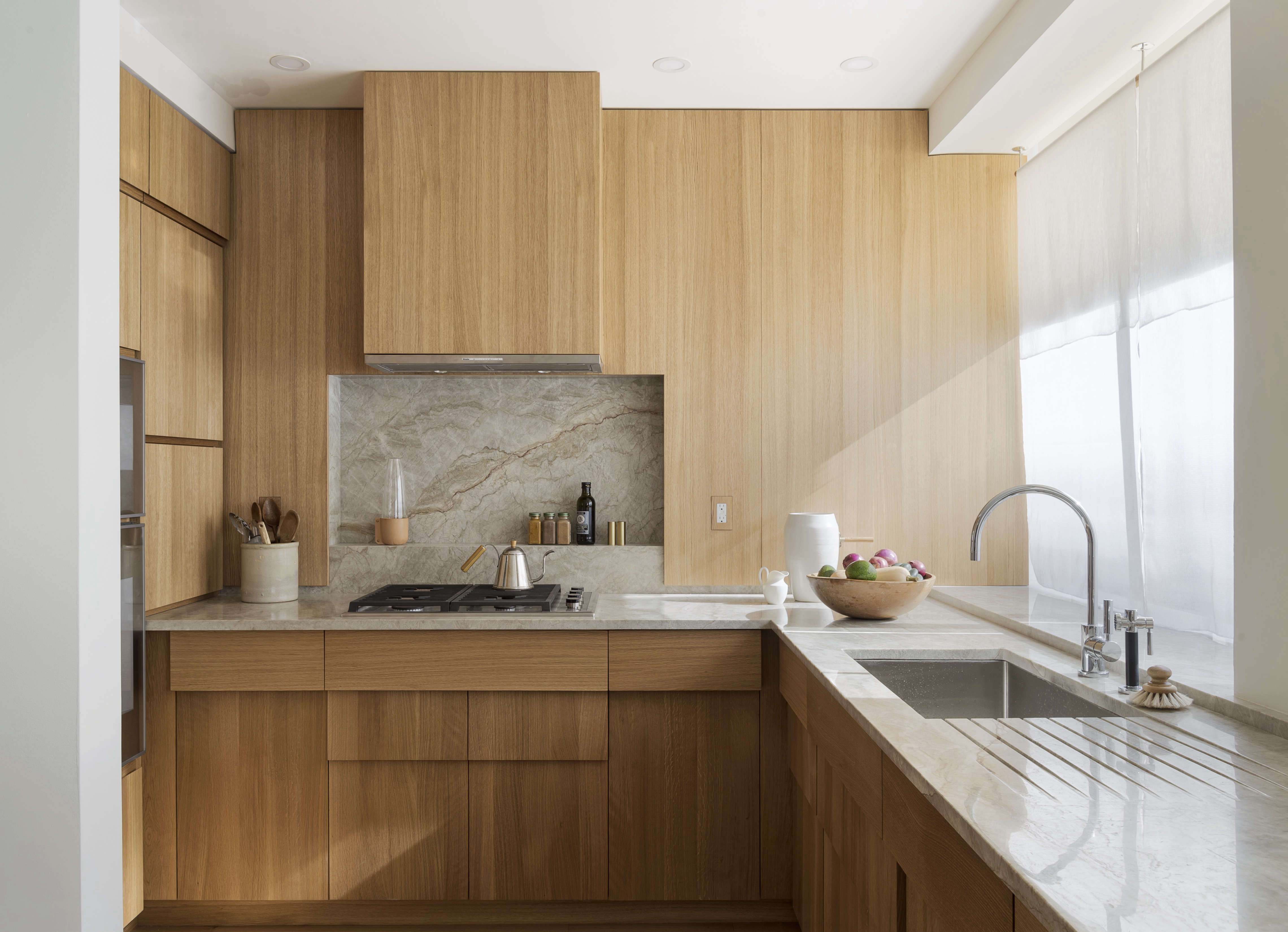 Stepped oak cabinets in a compact kitchen remodel in NYC by Workstead design, Matthew Williams photo