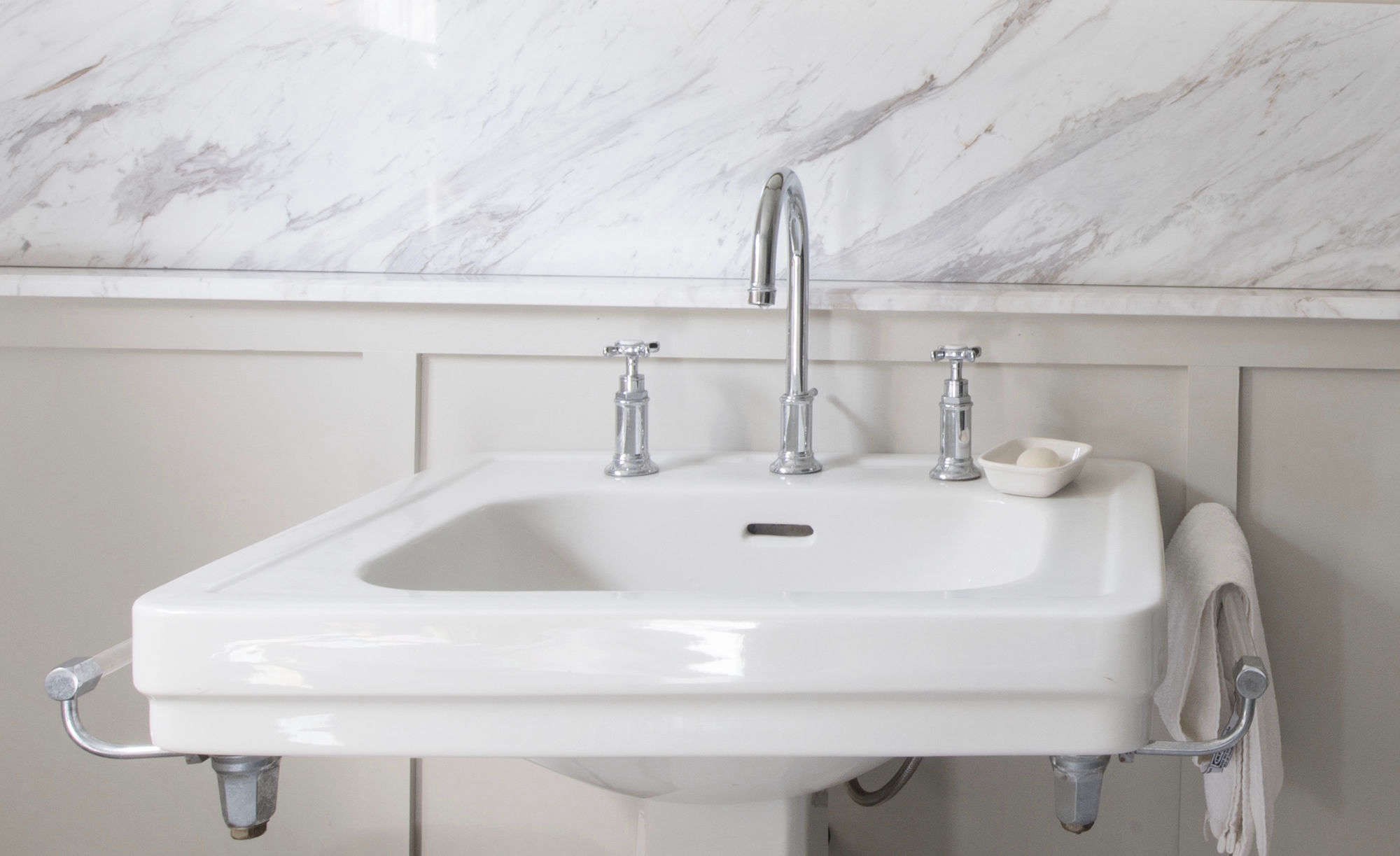 The vintage pedestal sink came with empty metalbracketsfor two towel rods, which Sosa sourced fromZaborski Emporium in Kingston, New York.