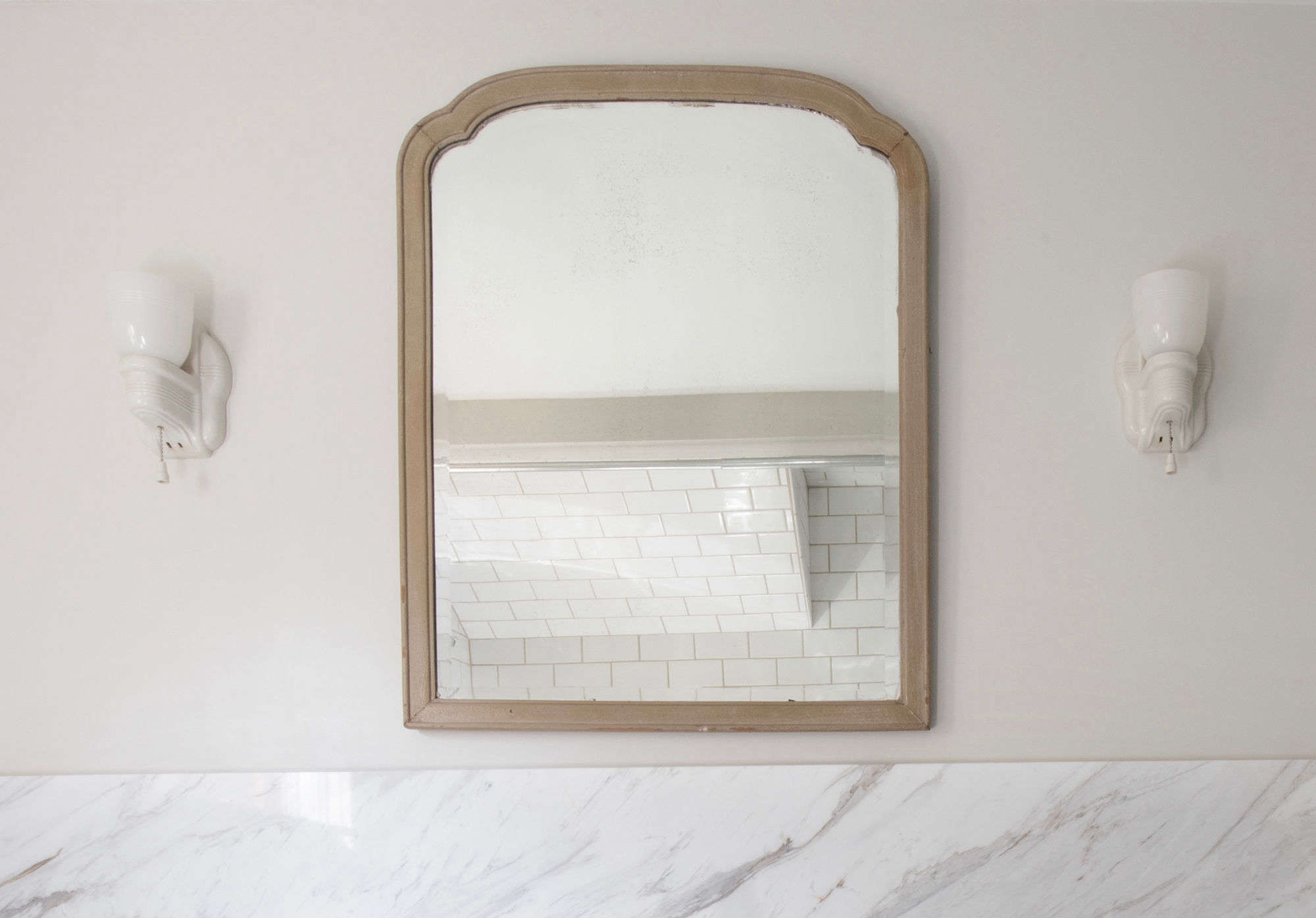 The wood-framed mirror was one of several found in the existing farmhouse; its mateis used in one of the bedrooms. It's flanked by two vintage porcelain sconces with glass shades, sourced and rewired fromSeattle Building Salvage.