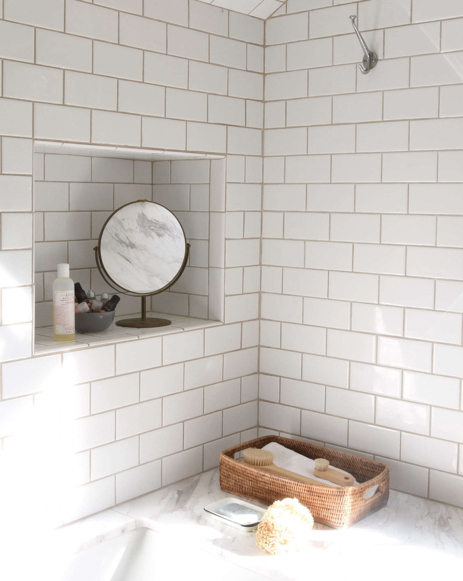 A recessed tile niche holdstoiletries and a fiber basket keeps scrub brushes and spare washclothshandy.