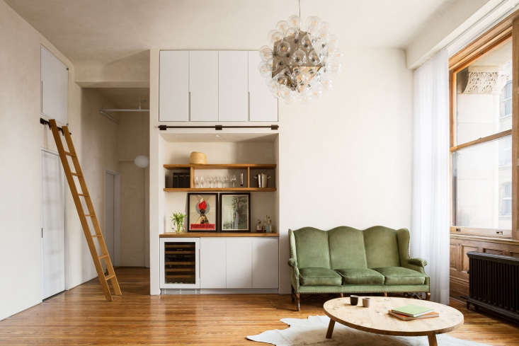 In the living room, a sliding libraryladder is suspendedfrom a custom rail over the bathroom door. The small access door above the ladder leads to a mechanical room.