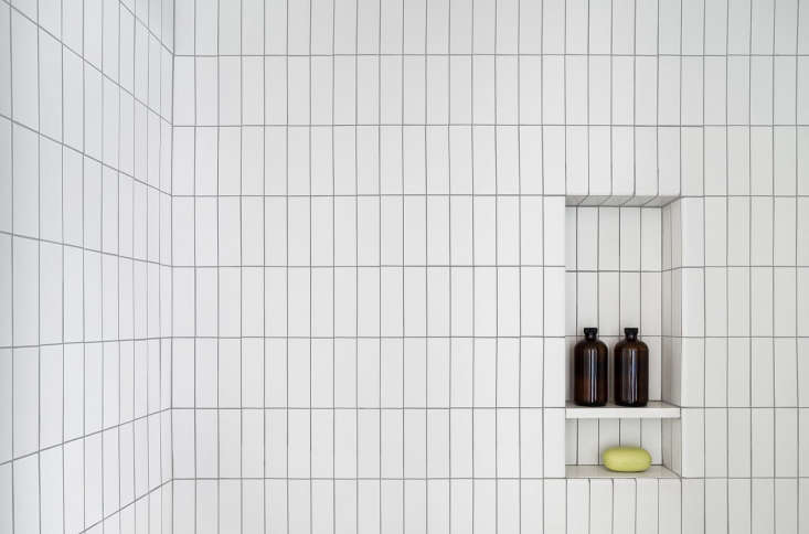 Tall and narrow niched shelving accentuates the vertical tiles (from Heath Ceramics) in this bathroom. Photograph byDevon Banks, courtesy of Denise Lee Architect, fromBefore & After: A Gramercy Park Apartment Transformed.
