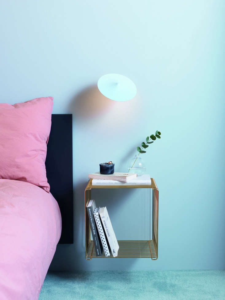 Verner Panton Wire Cube used as a bedside table. It's shown in a limited edition gold finish from Montana of Denmark.