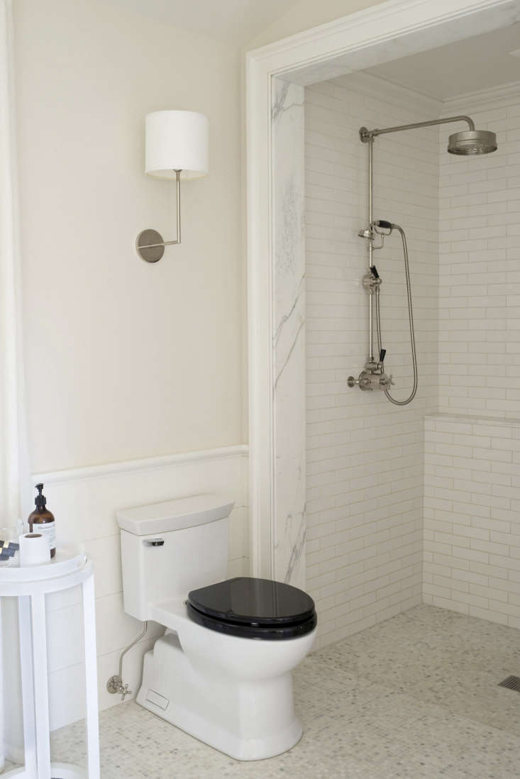 The bathroom floor tile is half-inch Carrara marble, and the shower fixture is also from Lefroy Brooks.