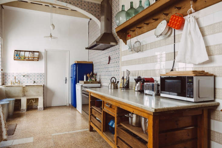 A kitchen by Spanish firm Quintana Partners has a simple wooden dish drying rack mounted over the sink. See a roundup of our favorite kitchens by the firm at Kitchen of the Week: Embracing the Old with Quintana Partners.