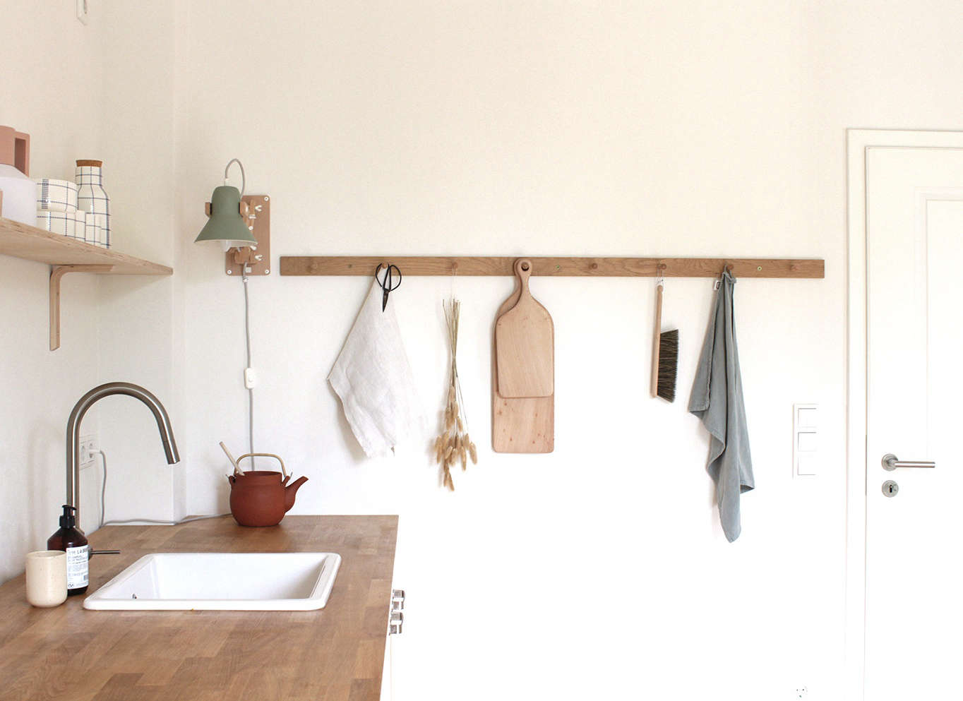 Shaker peg rail used for hanging accessories in the kitchen of illustrator/graphic designer Swantje Hinrichsen, Munster, Germany.
