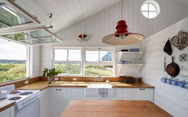 The light fixtures are all vintage; a double sconce from Amsterdam and a red barn light from 1st Dibs (for something similar, look to Barn Light Electric).The countertops are oak finished with a marine varnish. On the white electric range sits a Kaiko One-Handle Pan by Japanese designer Makoto Koizumi.
