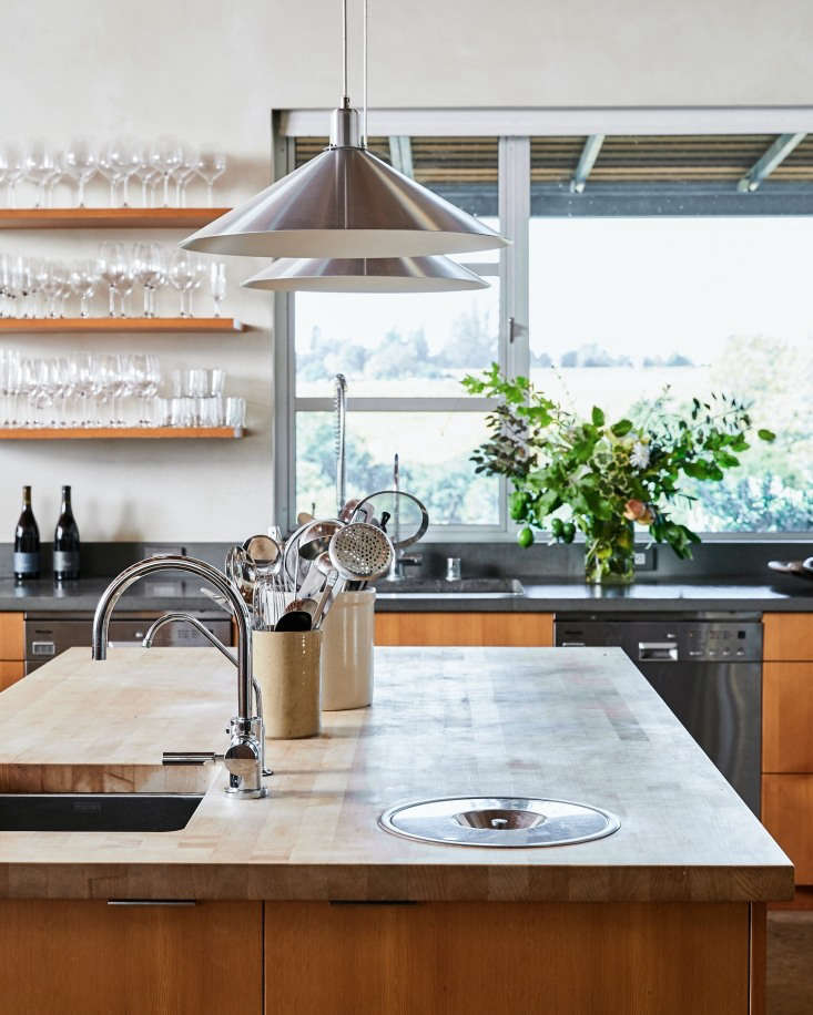 A large central island in the Sebastopol kitchen of winemaker Stephen Singer and his partner Michel Boynton, proprietors of Baker Lane Vineyards, features a butcher block countertop and integrated sink and compost pail. Photograph by Daniel Dent for Remodelista, from Kitchen of the Week: Part Tasting Room, Part Home Kitchen at Baker Lane Vineyards in Sonoma.
