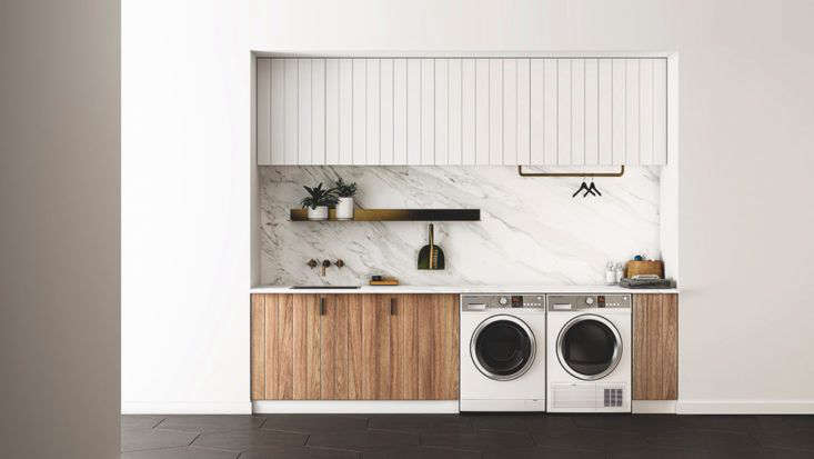 Luxe marble laundry room design by Fisher & Paykel with built-in cabinet storages and side-by-side washer dryer.