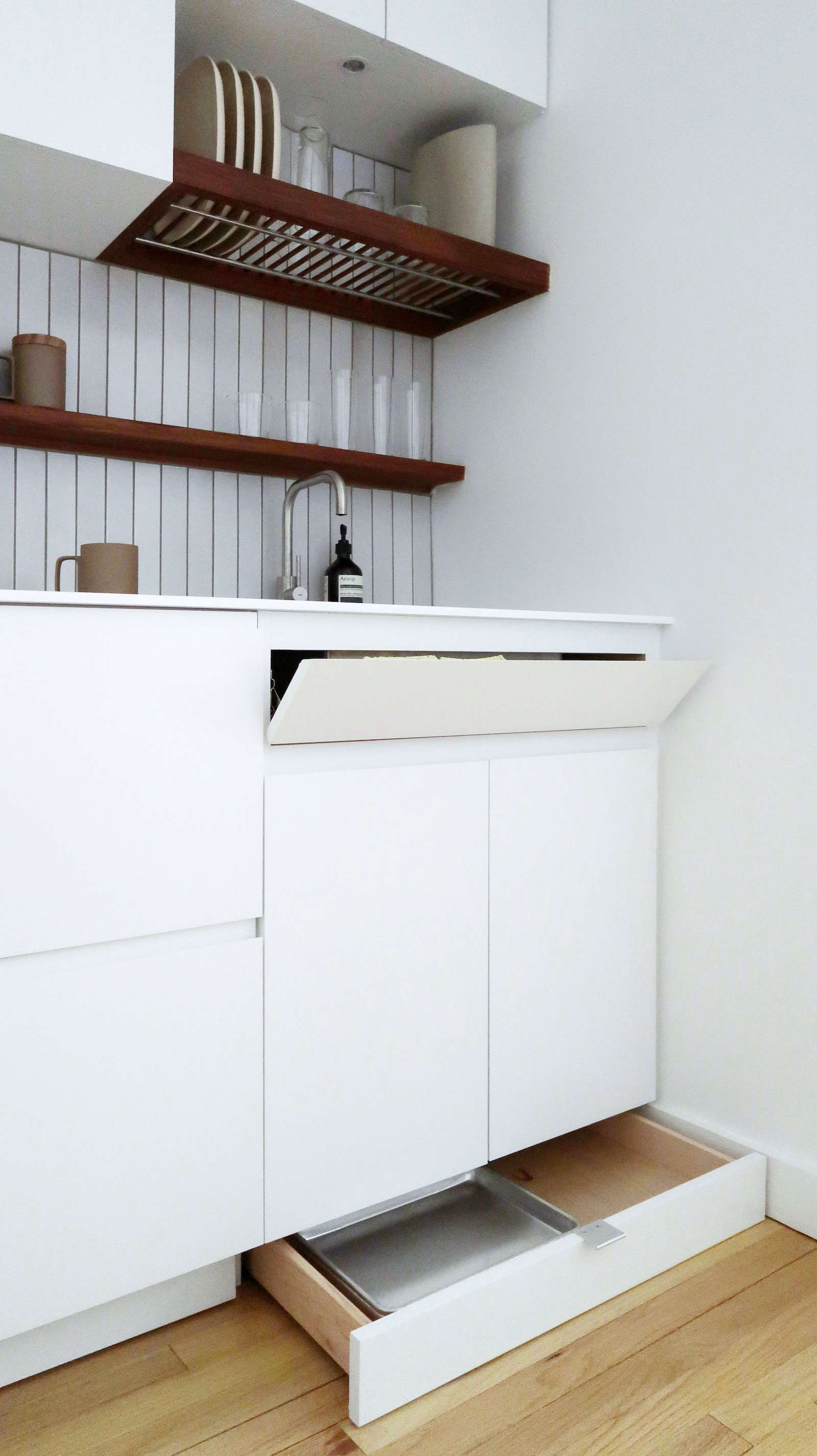 """The cabinet fronts are flat MDF panels with a sprayed, white lacquer finish. The toe kick drawers have stainless steel edge pulls (""""because they are basically invisible""""), and the cabinets have recessed bevels that serve as pulls."""