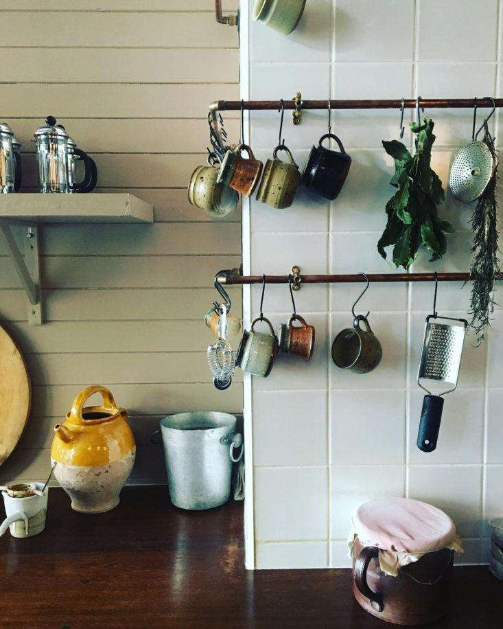 The staff uses the pipes-turned-rails to hang utensils, cups, and dried (or drying) herbs.