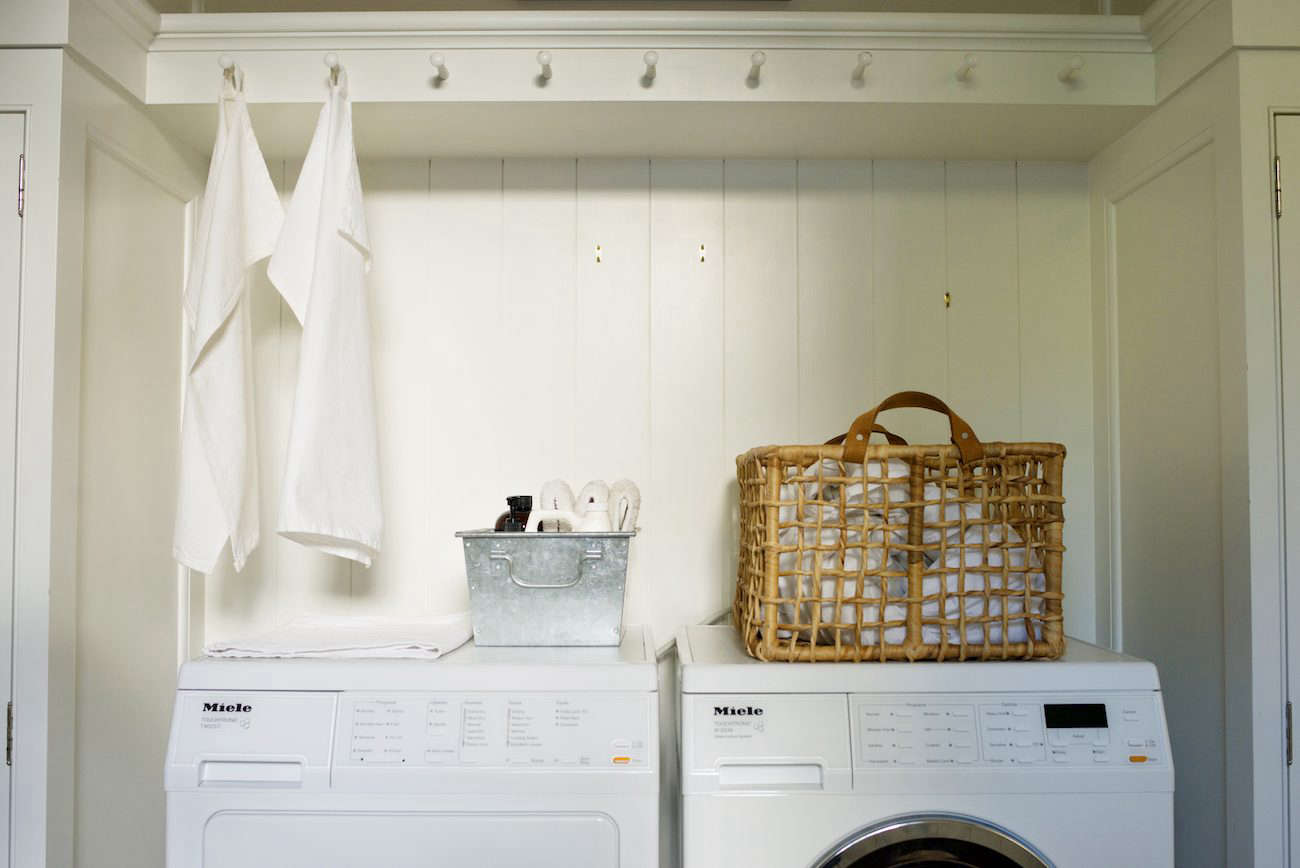 Barbara's laundry area, part of the mudroom, has Shaker peg hooks, laundry essentials organized in a steel bin, and a wicker and leather-handled laundry bin.