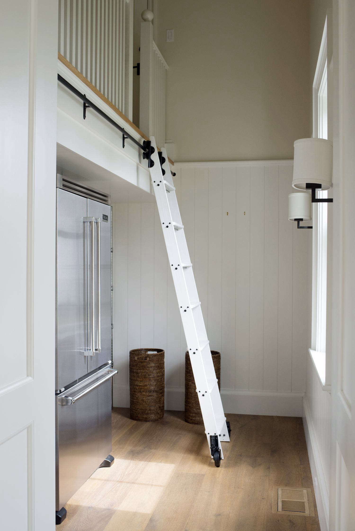 A rolling ladder inside Barbara's kitchen pantry is not for reaching overflow dry goods; rather, it leads to a guest bedroom that can be accessed both from the pantry and from outside. It's sited away from the daily circulation paths, but is there when Barbara's kids and their children come to visit.