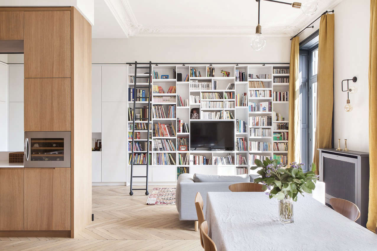 Architect Camille Hermand designed a full-height bookcase lacquered in Farrow & BallStrong White for this family room. It has acustom black metal sliding ladder and storage cabinets that wrap around the wall. SeeIn Paris, a Grand Apartment Gets an Update for a Modern Family. Photograph byHervé Goluza.