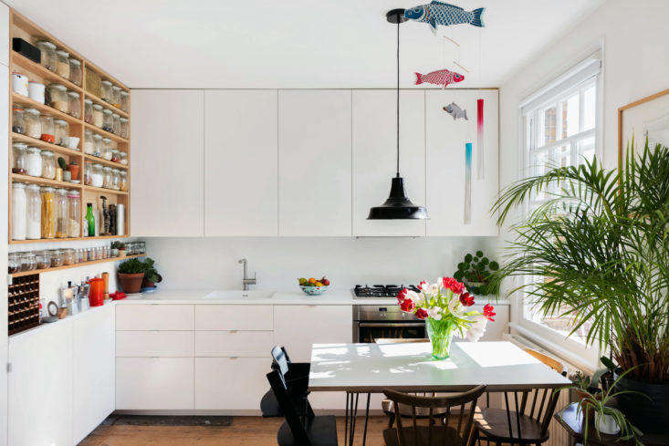 Eat in kitchen with dining table and white Ikea cabinets in London apartment