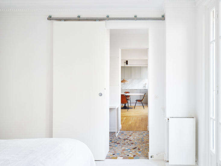 The functional hallway continues from the office into the bedroom, which is marked by the original wood flooring, painted white.