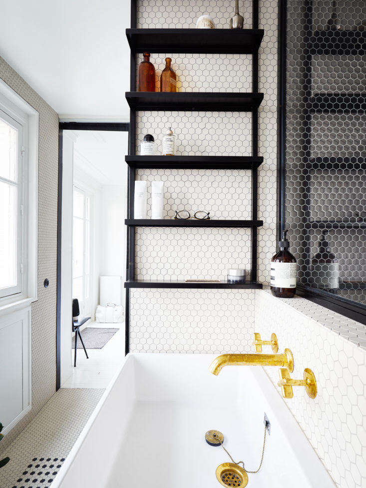 Because a mirror above the sink wasn't necessary, Septembre applied the same shape as an interior picture window looking into the black tile-lined shower.