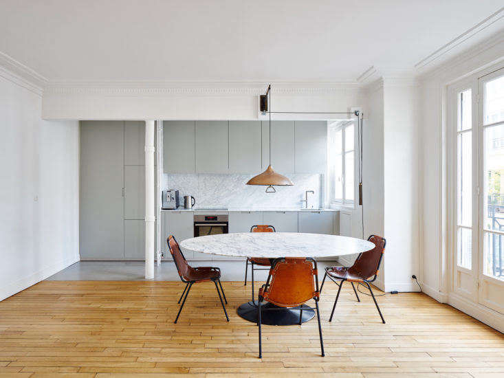The kitchen's gray laminate cabinets match its gray concrete floor, while the white marble backsplash matches the white marble top of the Saarinen Round Dining Table in the dining room.