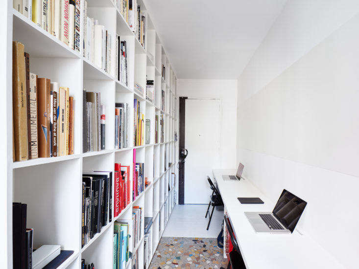 A full-height, full-length bookcase installed along one wall of a narrow home office provides copious storage space for books and work material. Opposite, a built-in desk runs the length of the hallway, offering ample work space for two.