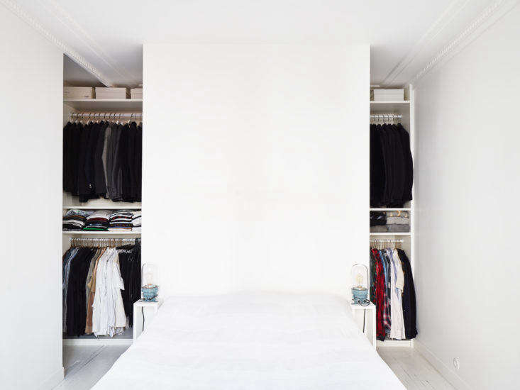 A drywall panel behind the bed functions as a headboard and a screen to partially shield the closet.