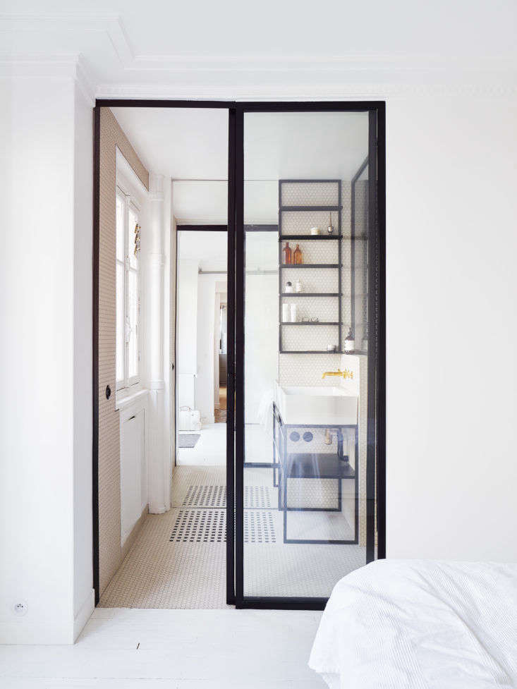 The bathroom shelving, sink, and door frames are all defined in black steel.