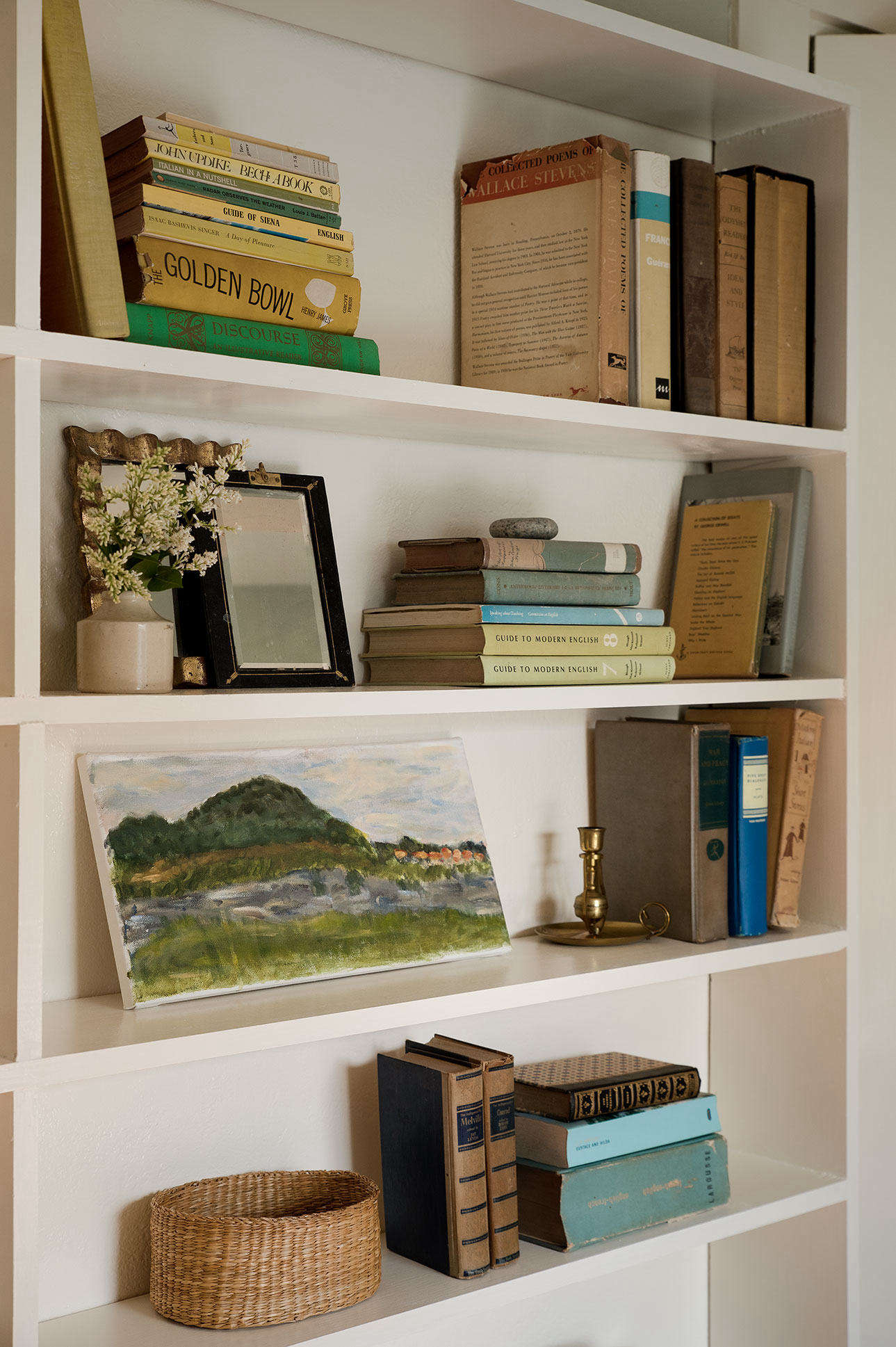 A bookshelf in Julie's Wellfleet house, post-decluttering. These volumes, as well as a landscape study by her daughter, survived the purge. Photograph byJustine Hand for Remodelista, fromBefore & After: A Low-Cost Summer Guest Room Makeover, Cape Cod Edition.