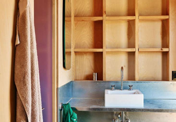In architect Malcolm Davis' weekend home, some of the framing in the bath was left exposed, creating incidental storage cubbies. Photograph by Joe Fletcher, courtesy of Malcolm Davis Architecture, from Aha! Design: The Unexpected Storage Opportunity Hidden Inside a Wall.