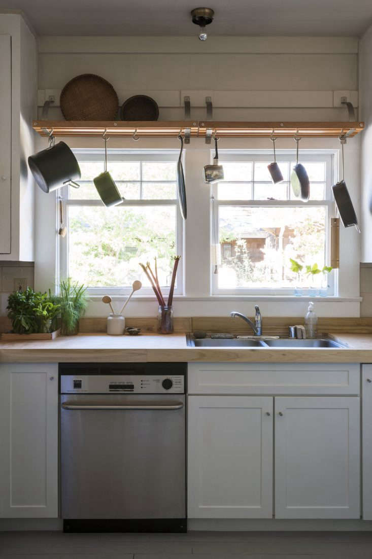 The dead space above the windows is the perfect place to hang a pot rack.