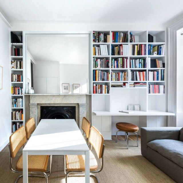 """""""A goal was to allow the apartment to seem as spacious as possible,"""" architect Daisy Ames explains. The one-room living and dining room feels larger than it is thanks to a large custom mirror over the fireplace and a rug cut to fit by The Perfect Rug. """"It helps frame the living space and create an axis from the entry to the terrace,"""" Ames says. The high/low furnishings were sourced on a budget: """"To balance the wood floors, we recommended Marcel Breuer's 1928 Cesca Chairs to go with a white Melltorp Ikea table."""" Photography by Alan Tansey, courtesy of @StudioAmes."""